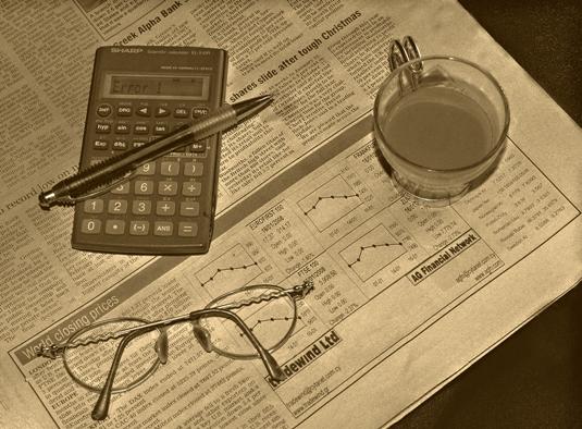 Газета с котировками акций, очки и чашка кофе