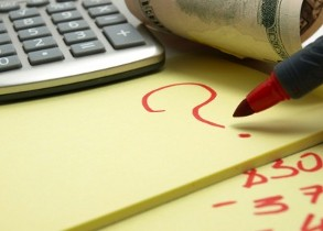 Расчеты и знак вопроса на желтой бумаге под калькулятором