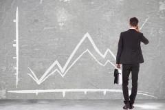 Инвестор перед доской с графиками индексов