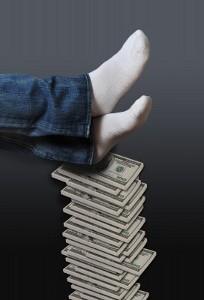 Человек отдыхает на стопке денег